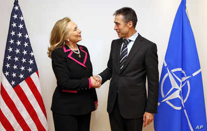 U.S. Secretary of State Hillary Rodham Clinton, left,  shakes hands with NATO Secretary-General Anders Fogh Rasmussen at the NATO headquarters in Brussels, December 4, 2012.