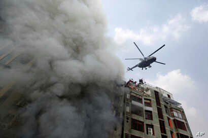 A chopper hovers to evacuate people stuck in a multi-storied office building that caught fire in Dhaka, Bangladesh, March 28, 2019.
