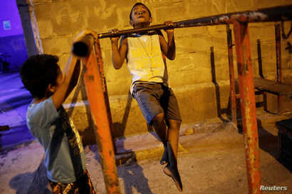 A boy does pull-ups from a metal bar outside the Luta pela Paz (Fight for Peace) boxing school, in the Mare favela of Rio de Janeiro, Brazil, June 2, 2016.