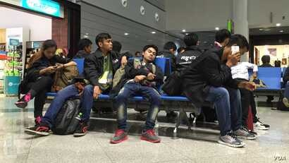 Cambodian workers at Phnom Penh International Airport awaiting to board a plane to Seoul, South Korea. (Poch Reasey/VOA Khmer)
