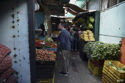 Jairo Colmenares a Venezuela's subway employee asks for prices of vegetables at the market in the west of Caracas, Dec. 29, 2018.