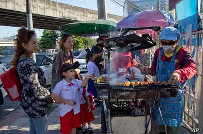 Schoolchildren gather around street vendors outside their school in Bangkok, Thailand, Nov. 1, 2018. A report by the United Nations Food and Agricultural Organization released Friday says some 486 million people are malnourished in Asia and the Pacif...