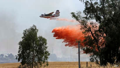 An air tanker drops a load of fire retardant while fighting a large grass fire, July 27, 2015, in Elverta, California.