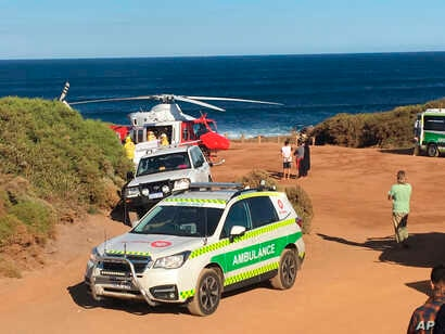 FILE - A rescue helicopter and other emergency vehicles are seen at the scene of the shark attack in Gracetown, Australia.