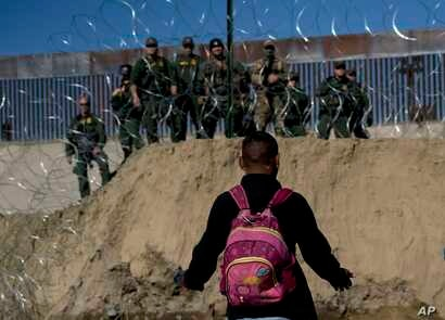 A Honduran migrant converses with U.S border agents on the other side of razor wire after they fired tear gas at migrants pressuring to cross into the U.S. from Tijuana, Mexico, Nov. 25, 2018.