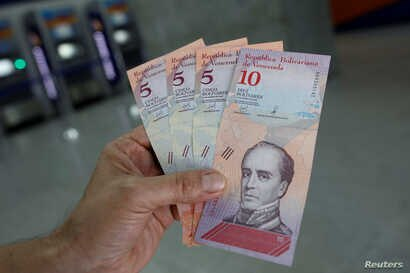 A man shows the new five and ten Bolivar Soberano (Sovereign Bolivar) bills, after he withdrew them from an automated teller machine (ATM) at a Mercantil bank branch in Caracas, Venezuela, Aug. 20, 2018.