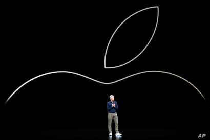 FILE- Apple CEO Tim Cook discusses the new Apple iPhones and other products at the Steve Jobs Theater during an event to announce new products in Cupertino, California, Sept. 12, 2018.