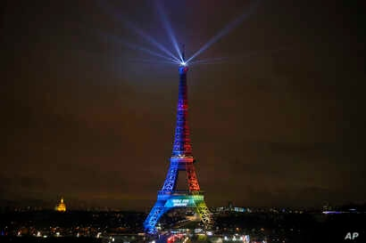 FILE - The Eiffel Tower is lit with colors for the Paris 2024 bid during the launch of the international campaign of the French capital as candidate for the 2024 Olympic summer games, in Paris, France, Feb. 3, 2017.