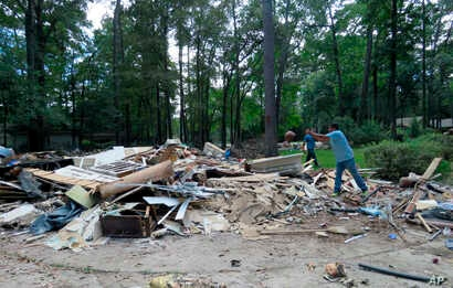 In this Sept. 26, 2017 photo, workers continue clearing debris from the home of Houston resident Chris Slaughter, whose house in the suburb of Kingwood was flooded by over 5 feet during Harvey's torrential rainfall.