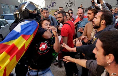 """A regional policeman removes a protester with an """"estelada"""" or independence flag, during a protest against a search for propaganda supporting Catalonia's independence referendum at the private postal service company Unipost in Terrassa, Spain, Sept. ..."""