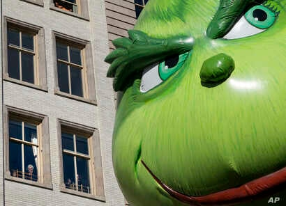 FILE - The Grinch balloon passes by windows of a building on Central Park West during Macy's Thanksgiving Day Parade in New York, Nov. 23, 2017.