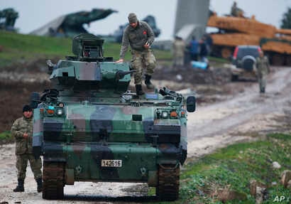 FILE - Turkish soldiers on an armored personnel carrier secure a staging area for  troops preparing their tanks to enter combat and join a military offensive on a Kurdish-held enclave in northern Syria, in Hatay province, Turkey, near the the border ...