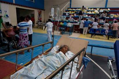 A 71-year-old woman, who was injured when a wall collapsed on her in Thursday's massive earthquake, receives treatment in a medical ward set up on a school's basketball court, in Juchitan, Oaxaca state, Mexico, Sept. 9, 2017. Juchitan General Hospita...