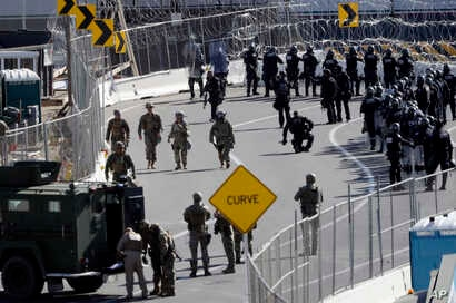 U.S. military personnel and Customs and Border Protection officers gather along the southbound lanes of the San Ysidro port of entry, Nov. 25, 2018, in San Diego, California, at the U.S. border with Mexico.
