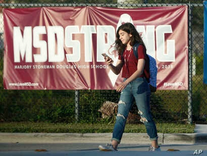 """A student walks past an """"MSDSTRONG"""" banner on the way to class at Marjory Stoneman Douglas High School in Parkland, Fla., Aug. 15, 2018"""