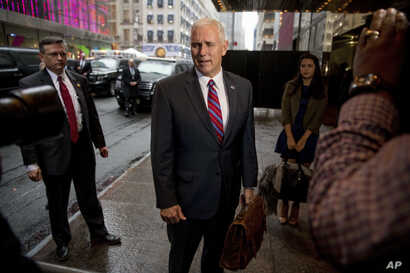 Vice President-elect Mike Pence, accompanied by his daughter Audrey, right, speaks to reporters as he arrives at Trump Tower in New York, Jan. 3, 2017.