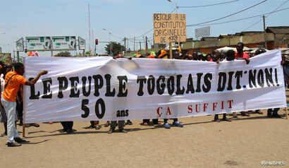 """Opposition supporters take part during a protest calling for the immediate resignation of President Faure Gnassingbe in Lome, Togo, Sept. 20, 2017. The banner reads: """"Togolese people say: No. 50 years, enough."""""""