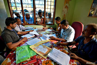FILE - People wait to check their names on the draft list at the National Register of Citizens (NRC) centre at a village in Nagaon district, Assam state, India, July 30, 2018.