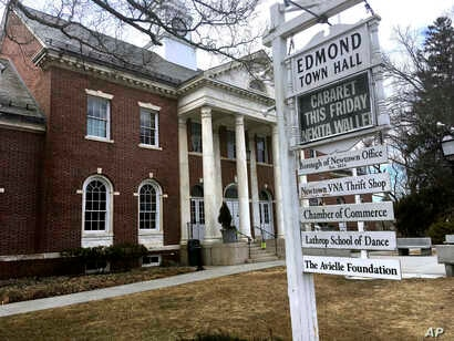 Signs hang outside Edmond Town Hall, a building that houses a community theater and offices, in Newtown, Conn., March 25, 2019. Jeremy Richman, father of Sandy Hook Elementary school shooting victim Avielle Richman, was found dead Monday at the build...