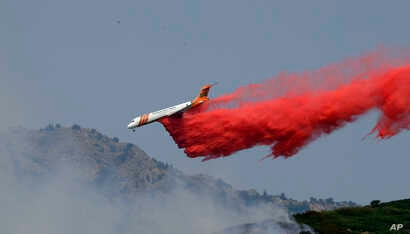 A heavy tanker drops retardant on a wildfire in Weber Canyon, Sept. 5, 2017, near Ogden, Utah.