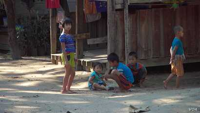 Karen children play a game in front of a local home in the town of Shwe Koko in Karen state, Myanmar.