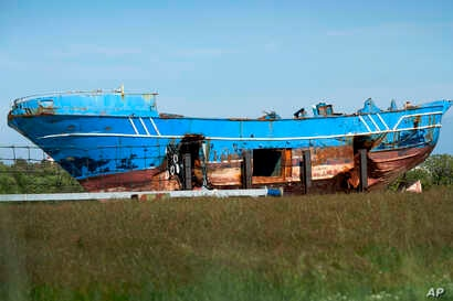 FILE - The wrecked fishing boat that capsized and sunk on April 18, 2015, off the coast of Libya, lies outside a NATO base in the Sicilian town of Mellili, Italy, Oct. 8, 2016.