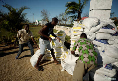 Workers offload food aid from a South African National Defense Force helicopter in the aftermath of Cyclone Idai in Buzi, near Beira, Mozambique, March 25, 2019.