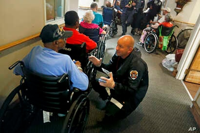 Mathew Meyer of the Nebraska Task Force 1 urban search and rescue team, right, talks with Korea war veteran Roman Wiggs, 87, as they evacuate an assisted living facility to a church as a precaution against potential flooding the city could see from t...