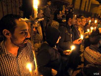 """Egyptian copts seen lighting candles during a vigil in front of the """"Botrosia"""" church, 35 were announced injured in Abbassya as they attended a vigil in Cairo, Dec. 11, 2016."""