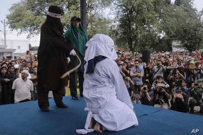 A Shariah law official whips a woman who is convicted of prostitution during a public caning outside a mosque in Banda Aceh, Indonesia, April 20, 2018. Indonesia's deeply conservative Aceh province on Friday caned several unmarried couples for showin...