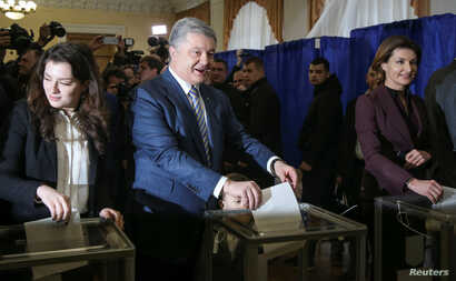Ukraine's President and presidential candidate Petro Poroshenko and his family members, wife Maryna, daughter Yevhenia and grandson Petro, cast ballots at a polling station during a presidential election in Kiev, Ukraine March 31, 2019. REUTERS/