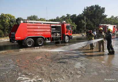 Afghan fire-fighters clean the site of a suicide attack in Kabul, Afghanistan, June 20, 2016.
