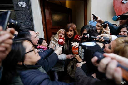 Former President Cristina Fernandez is surrounded by media outside her home as she leaves for a court hearing, in Buenos Aires, Argentina, Aug. 13, 2018.