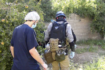 A U.N. chemical weapons expert (R) gathers evidence at one of the sites of an alleged poison gas attack in the southwestern Damascus suburb of Mouadamiya, August 26, 2013.