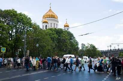 Russian Orthodox believers cross the road to line up to kiss the relics of Saint Nicholas that were brought from an Italian church where they have lain for 930 years, in the Christ the Savior Cathedral in Moscow, Russia. The photo was taken on May 26...