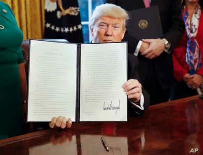 President Donald Trump holds up an executive order in the Oval Office of the White House, Feb. 3, 2017. The executive order that will direct the Treasury secretary to review the 2010 Dodd-Frank financial oversight law.