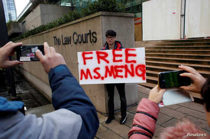 A man holds a sign outside of the B.C. Supreme Court bail hearing of Huawei CFO Meng Wanzhou, who is being held on an extradition warrant in Vancouver, British Columbia, Canada December 10, 2018.