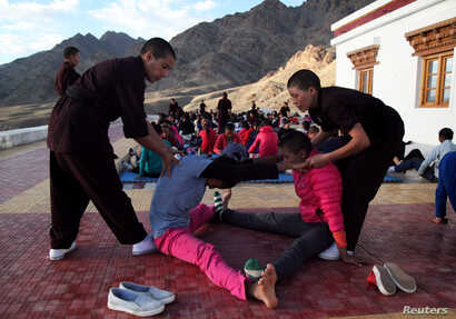 Buddhist nuns help participants stretch their muscles during a five-day workshop teaching young women the martial art of Kung Fu, in Hemis region in Ladakh, India, August 18, 2017.