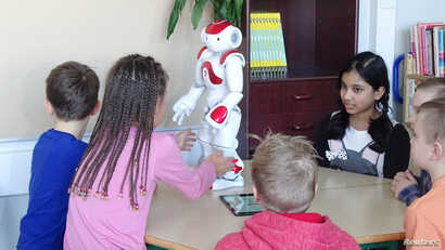 FILE - Students use a language-trainer robot, Elias, during their lesson at the school in Tampere, Finland, March 27, 2017.