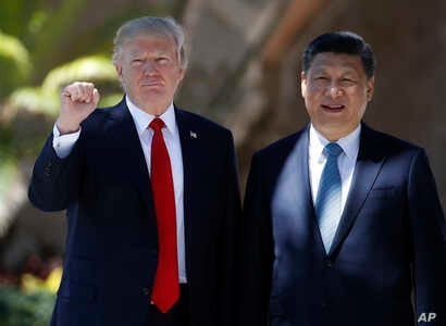 President Donald Trump and Chinese President Xi Jinping pause for photographs at Mar-a-Lago, Friday, April 7, 2017, in Palm Beach, Fla. Trump was meeting again with his Chinese counterpart Friday, with U.S. missile strikes on Syria adding weight to h...