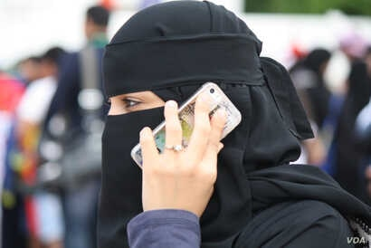 A woman uses a smartphone in Jeddah, Saudi Arabia, Jan. 28, 2016. Saudi Arabia and Iran accuse each other of human rights abuses against their own citizens. International rights groups say both countries have trampled on civil liberties, repressed wo...