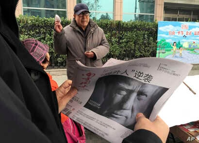 "FILE - A Chinese man holds up a Chinese newspaper with the front-page photo of Donald Trump and the headline ""Outsider counter attack"" at a newsstand in Beijing, China, Nov. 10, 2016. China has pledged to ""firmly defend its legitimate rights and inte..."