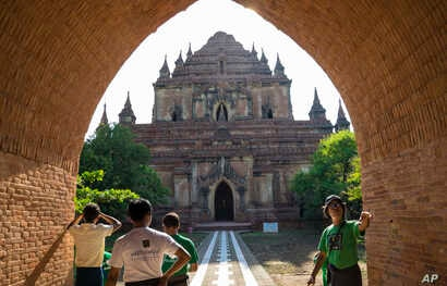 FILE - People watch the Sulamani Guphaya temple, which was damaged after a strong earthquake hit Bagan, Myanmar.