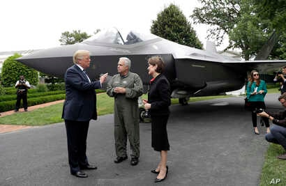 """President Donald Trump talks with Lockheed Martin president and CEO Marilyn Hewson and director and chief test pilot Alan Norman in front of a F-35 as he participates in a """"Made in America Product Showcase"""" at the White House, July 23, 2018."""