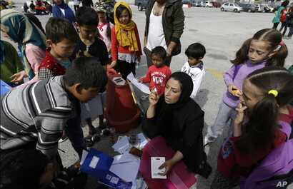 University teacher Ziaee Shole, center, speaks to Afghan children at the Athens port of Piraeus, on April 1, 2016.