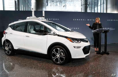 FILE - In this Thursday, Dec. 15, 2016, file photo, General Motors Chairman and CEO Mary Barra speaks next to a autonomous Chevrolet Bolt electric car, in Detroit. General Motors says it has built 130 self-driving Chevrolet Bolt electric cars at a fa...