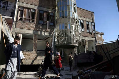 Afghans gather in front of the Shiite cultural center after a suicide attack in Kabul, Afghanistan, Dec. 28, 2017.
