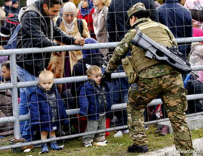 A member of the Slovenian army talks to migrants waiting at the Austrian border near the village of Sentilj, Slovenia, Oct. 25, 2015.