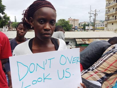 Gloria Maya Terrick holds a sign requesting the government to allow the students to help in the fight against Ebola, outside NGO headquarters, in Monrovia, Liberia, Sept. 29, 2014. (Benno Muchler/VOA)