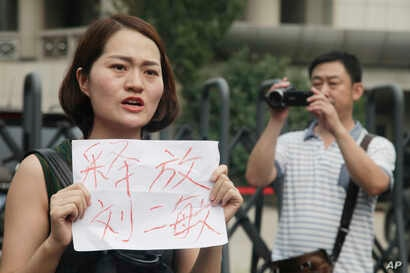 "FILE - In this Aug. 1, 2016 file photo, a man films Li Wenzu, left, wife of imprisoned lawyer Wang Quanzhang, holds a paper that reads ""Release Liu Ermin"" as she and others stage a protest in Tianjin, China."
